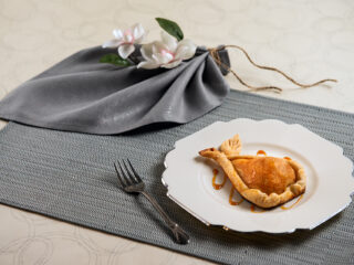 Gorgeous food photography of a dessert, Caramel Pie Pear. Beautifully plated on a silver trimmed ivory plate are the caramel pear pies. The plate is placed on a striped placemat in colors of blues, grays and ivory. A grayish silver fabric napkin is folded in a leaf shape, tied with twine and soft ivory flowers are tucked into the folds. A delicate lace trimmed tray with three Pear Pies also sets on a placemat. The set background is ivory with thin a delicately silver swirling pattern.