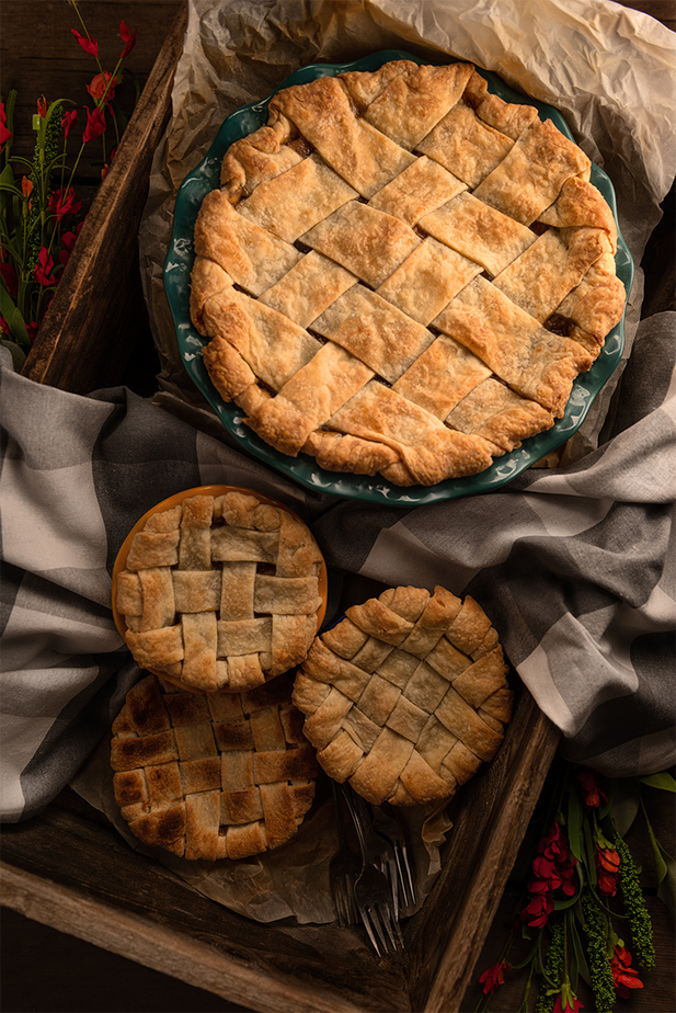 Apple Pie and three tarts arrange inside a wooden grape box with parchment paper and a kitchen towel with 3 forks