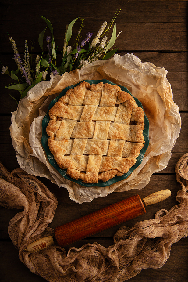 Lattice apple pie wrapped with parchment paper, flowers, vintage rolling pin and fabric draped setting on wooden grape tray.