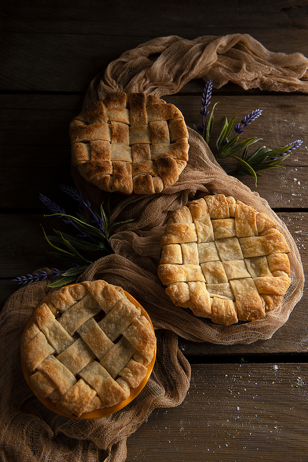 three tart sized apple pies with lattice top crust on grape tray with fabric and flowers.