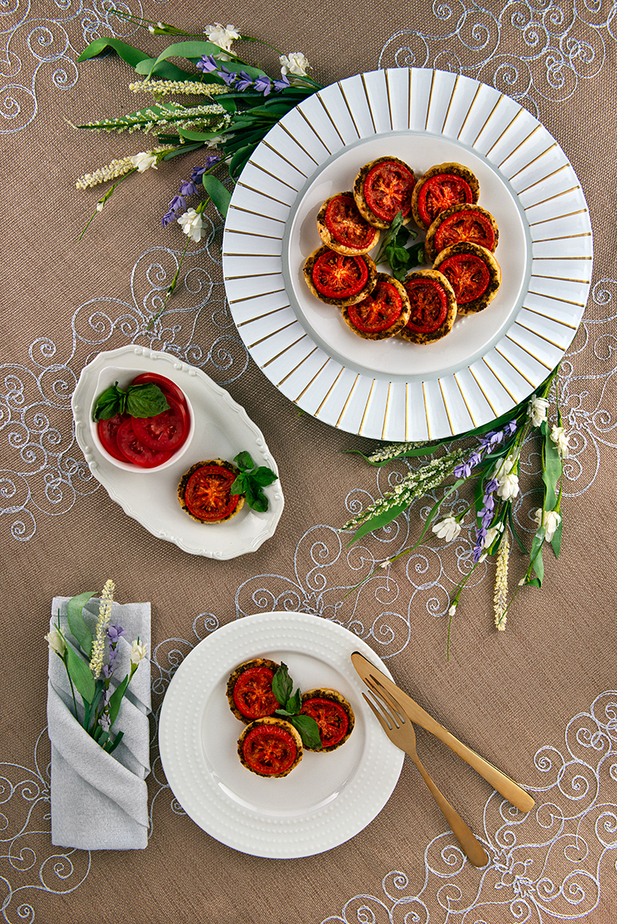 oven roasted tomatoes on puff pastry rounds, a white plate plated with three Tomato Puffs and a sprig of basil, small oval white tray with small white bowl holding fresh sliced tomatoes, one tray with plated tomato puffs and accented with a sprig of basil.