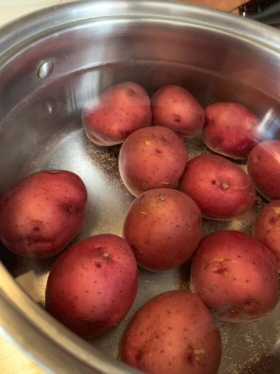 large pot of water, filled with red potatoes