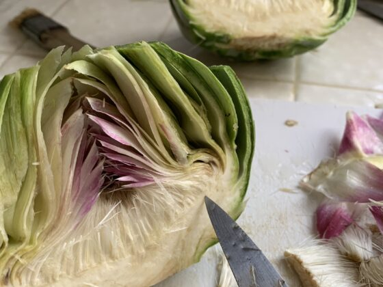 halved artichoke hearts on chopping board with paring knife