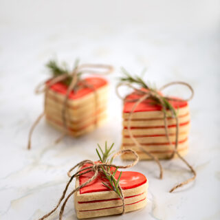 Three stacks of cookies, tied with twine and a spring of rosemary setting on a marble table.