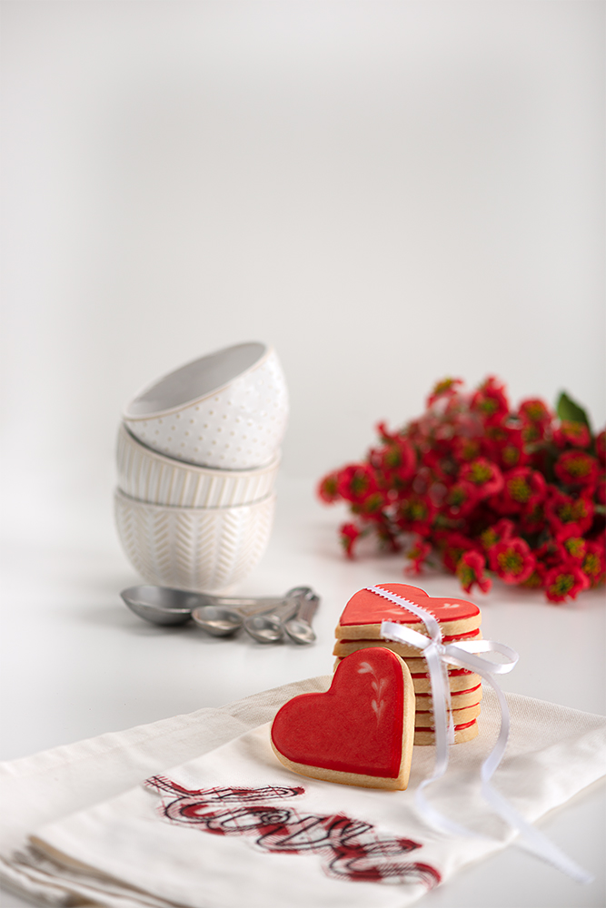 A stack of cookies placed on a kitchen towel, measuring spoons next to 3 small bowls and a bouquet of flowers.