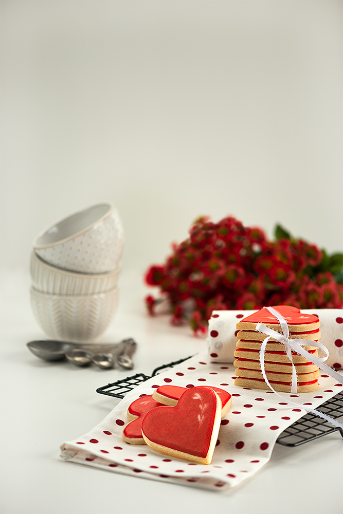 Cookies stacked on a kitchen towel setting on a bakers rack. 3 small bowls, measuring spoons and red bouquet of flowers.