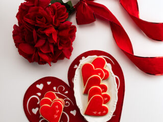 bouquet of roses, large felt heart with small tray of cookies on white table