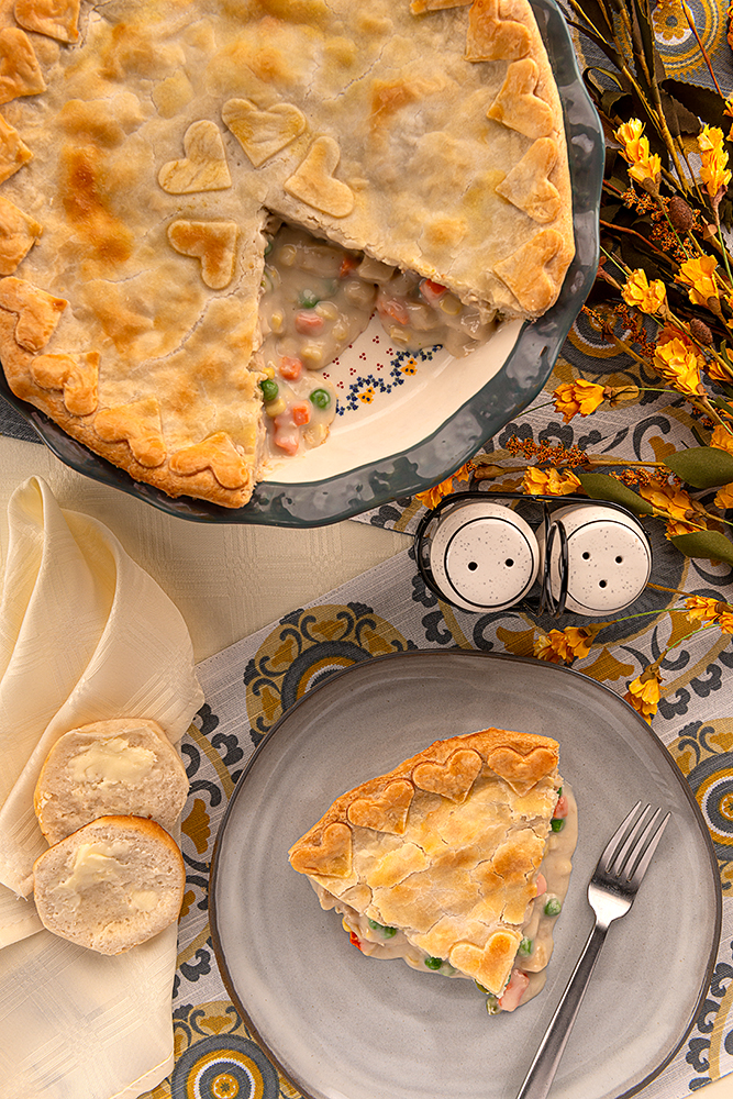A serving of chicken pot pie and a pie plate with chicken pot pie