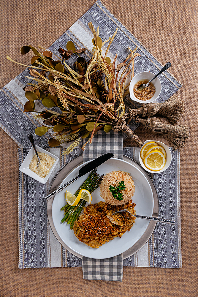 flowers on a table with plated chicken, rice and asparagus