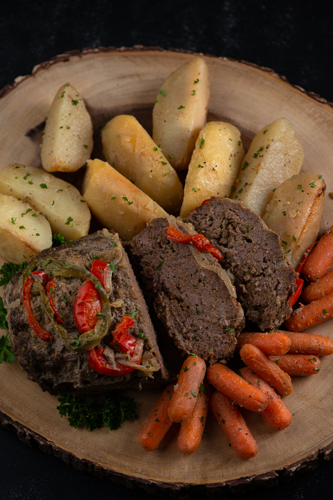 meatloaf, carrots and potatoes on a wooden platter