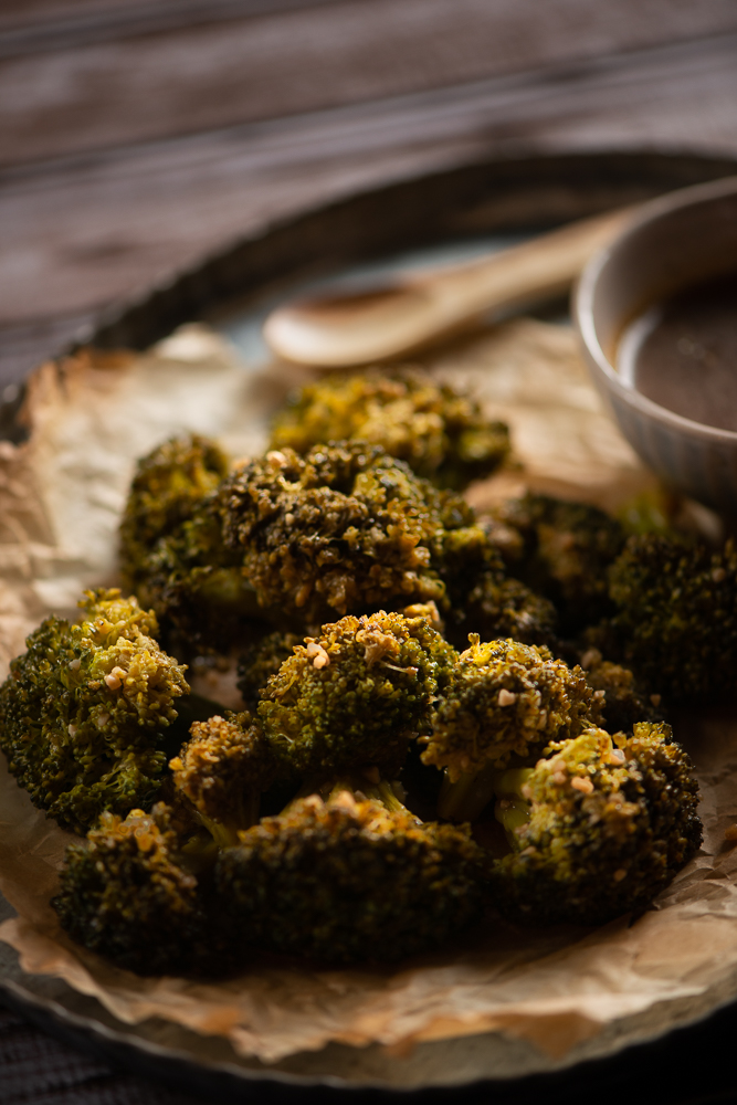 Sauteed broccoli setting on burned parchment paper in a tin serving tray