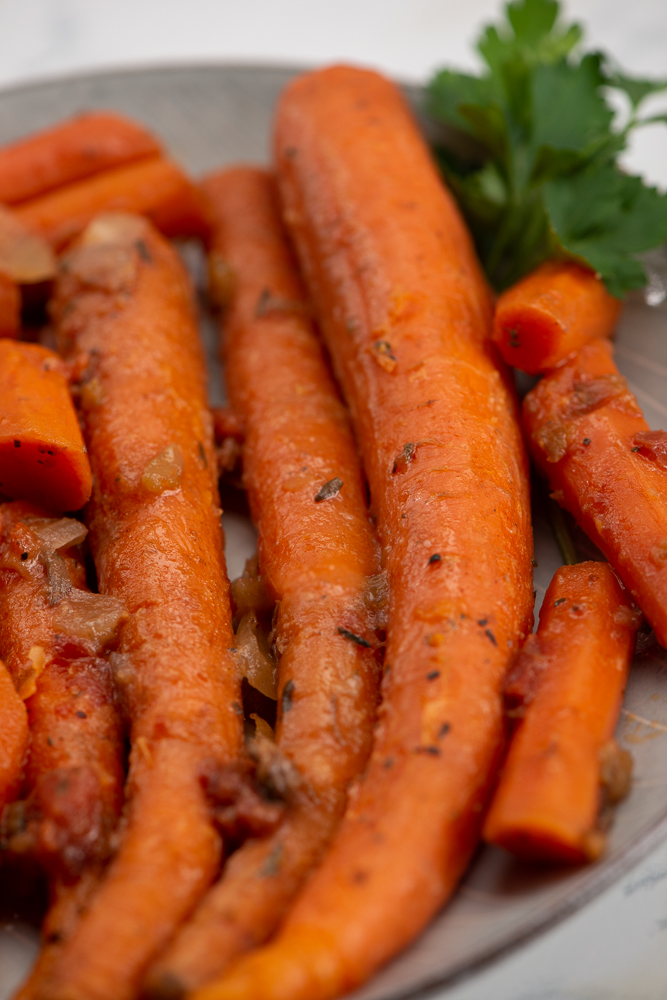 Close up of cooked carrots in a bowl.