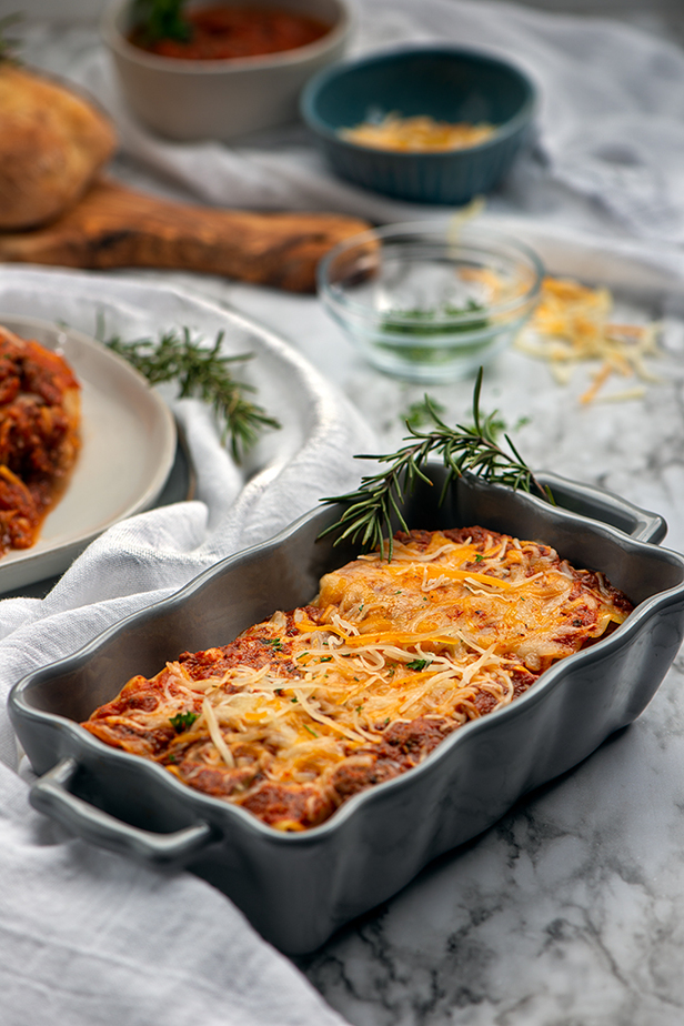 A marble table with tray of lasagna, plate of lasagna, small bowls of spaghetti sauce, shredded cheese and parsley.