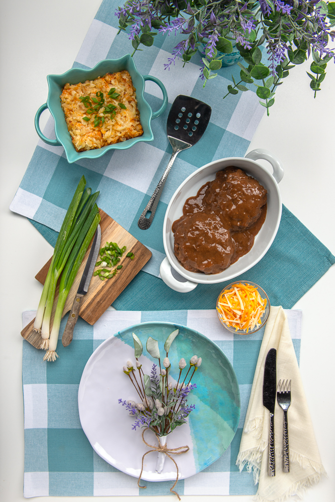 Table set with flowers, chopping board, green onions, serving bowls with hash brown casserole and salisbury steak.