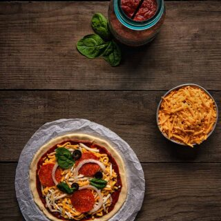 wood plank table with bowl of cheese mason jar with pizza sauce and uncooked pizza.