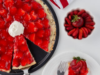 pizza pan of strawberry pizza, piece of strawberry pizza, sliced strawberries, plates and forks. Ripen Fruit