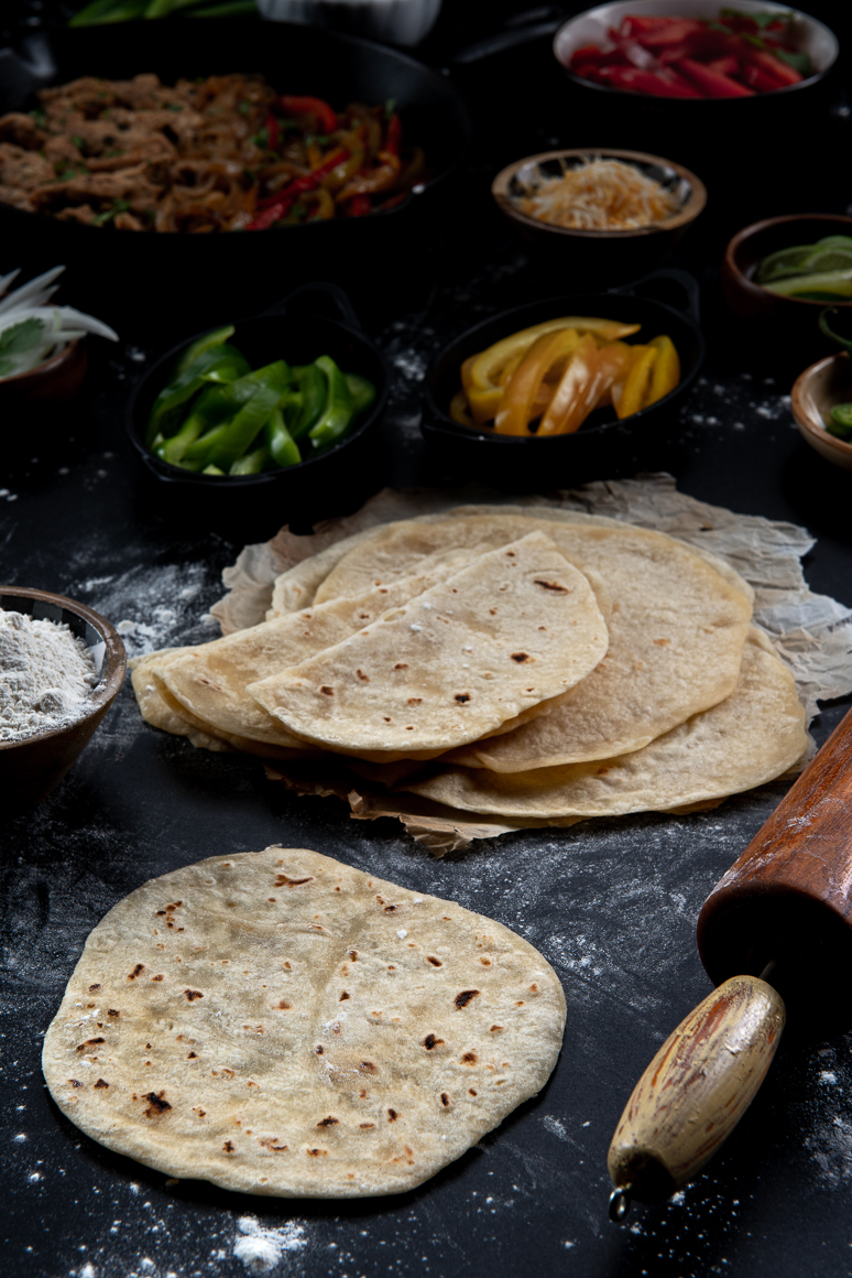Tortillas on a table with rolling pin and sliced peppers