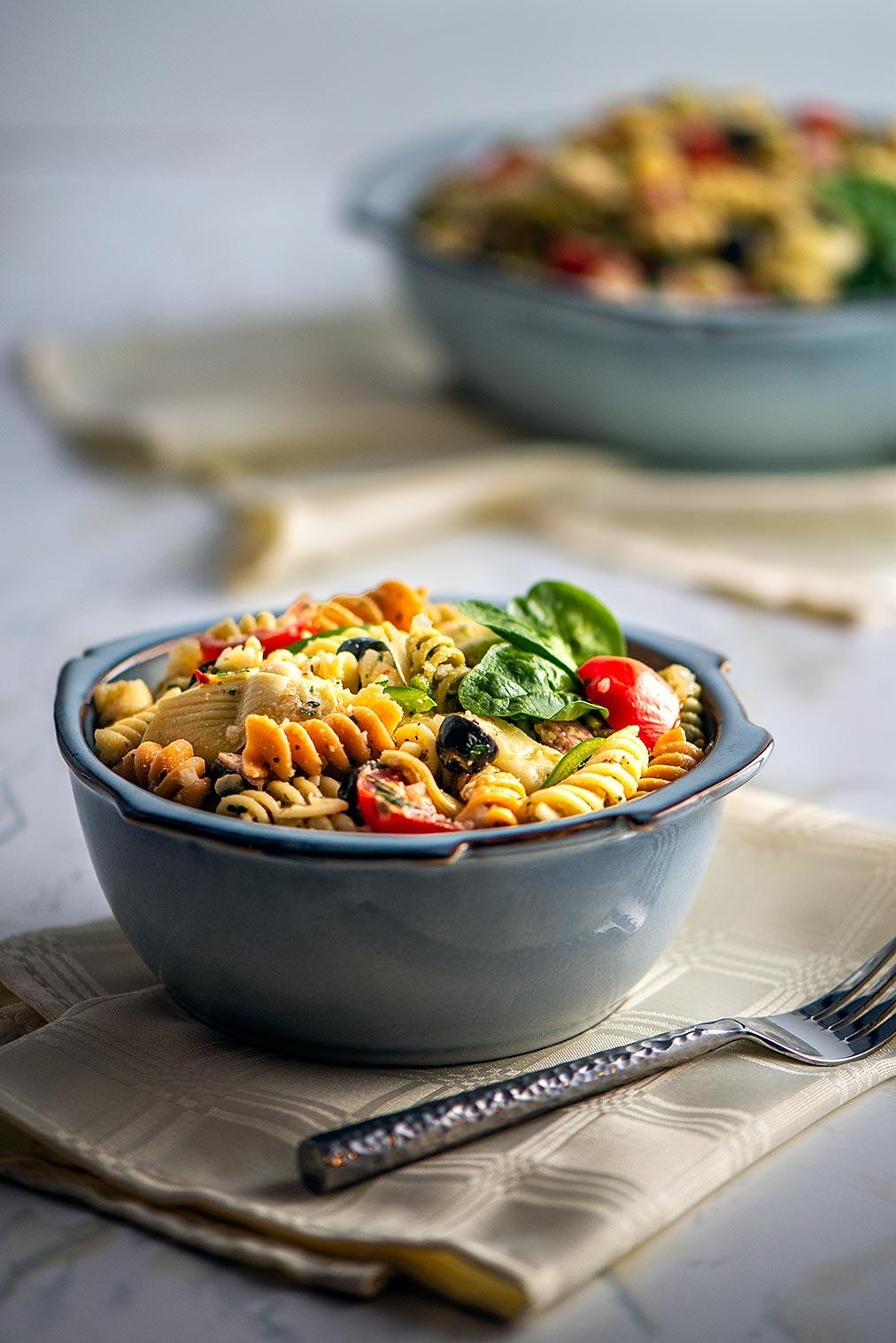 soup bowl of pasta salad and in the background a large serving bowl of pasta salad