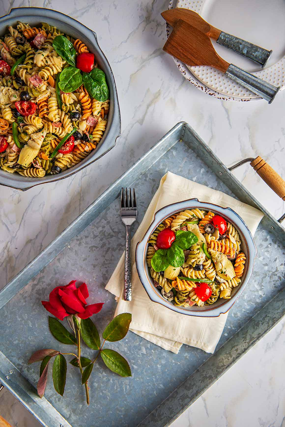 Serving tray with soup bowl of pasta salad, fork, napkin and a rose sitting on a marble table with a large serving bowl of pasta salad and serving spoons.