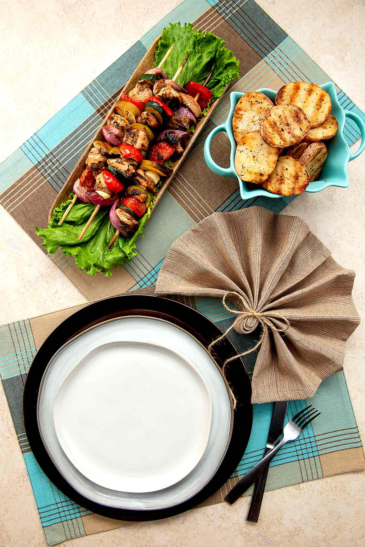 table setting and fan folded napkin. Tray of chicken & Veggie Kabobs and bowl of grilled rosemary potatoes.
