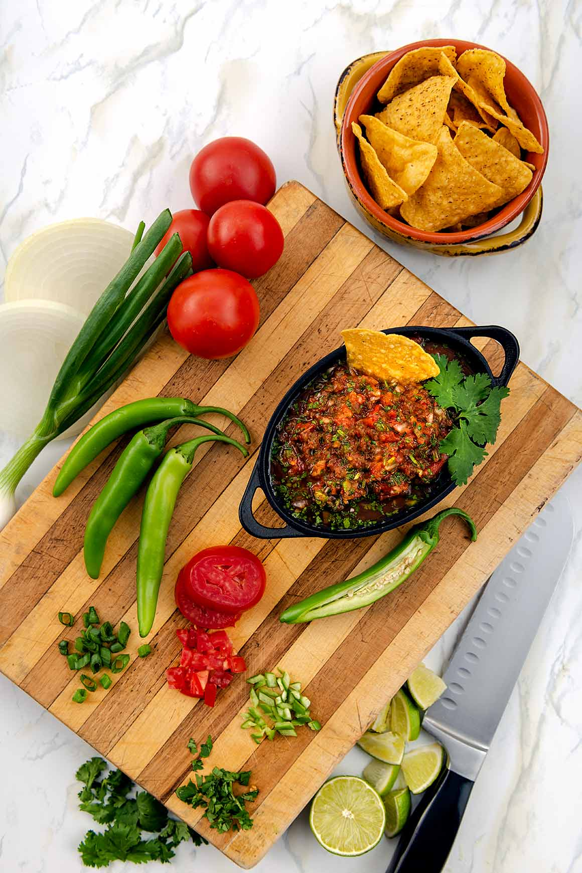 salsa on chopping board with fresh ingredients and chips.