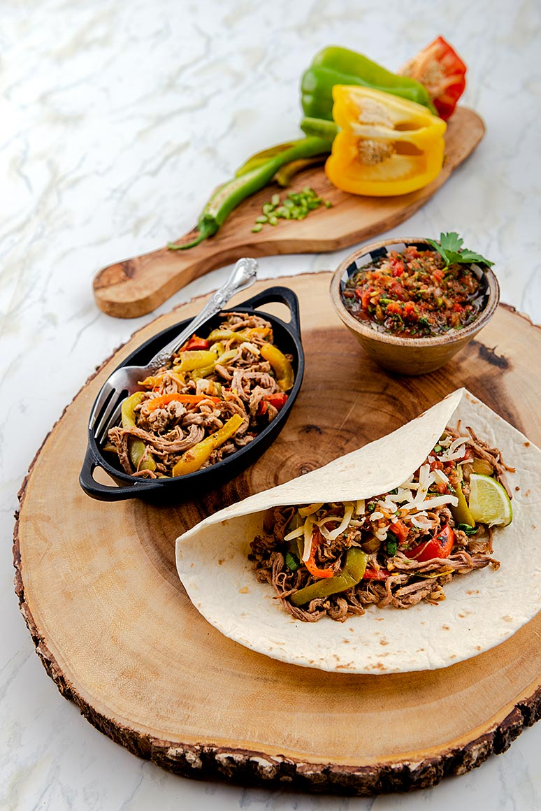 wooden charger with cast iron serving tray of beef fajita, small bowl of salsa and blour tortilla filled with beef fajita.