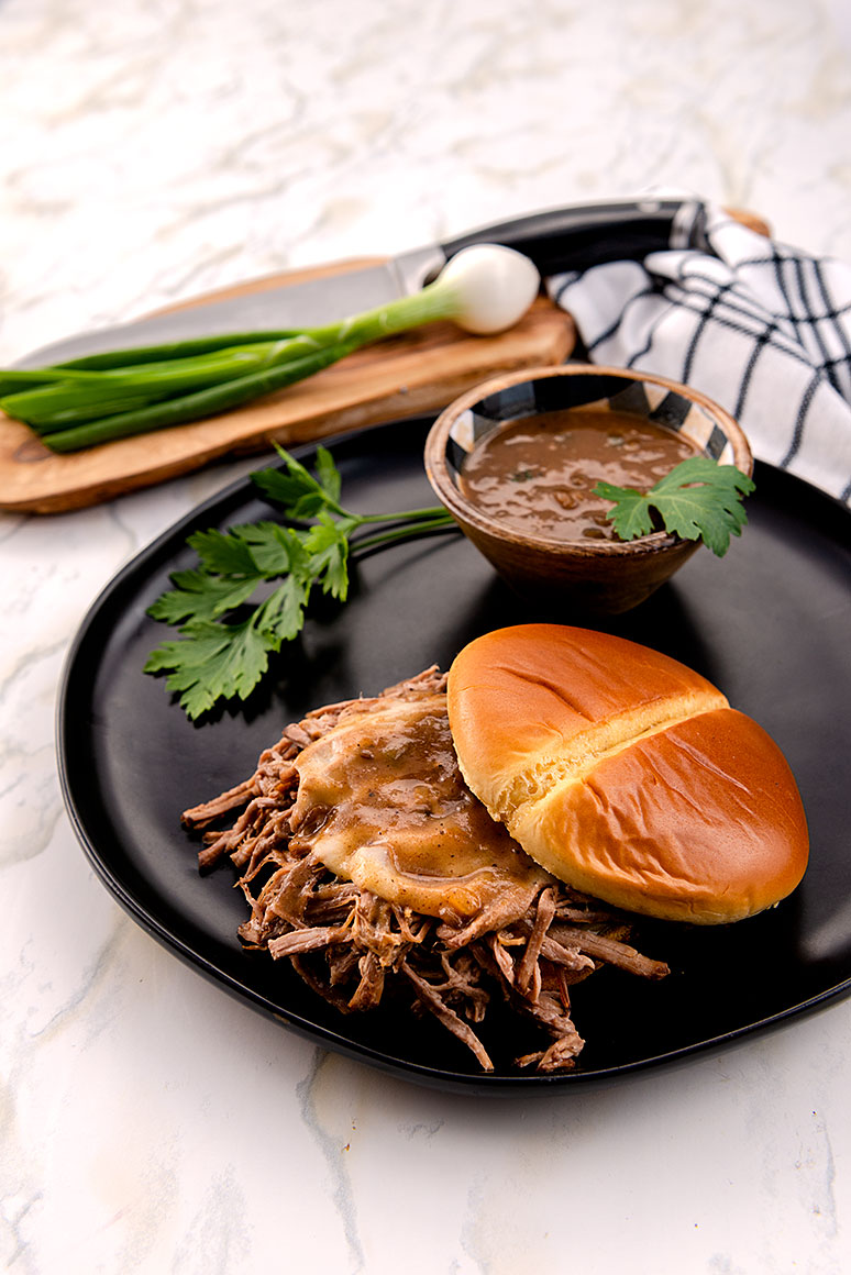 photo of french dip sandwich and chopping board, knife and scallion