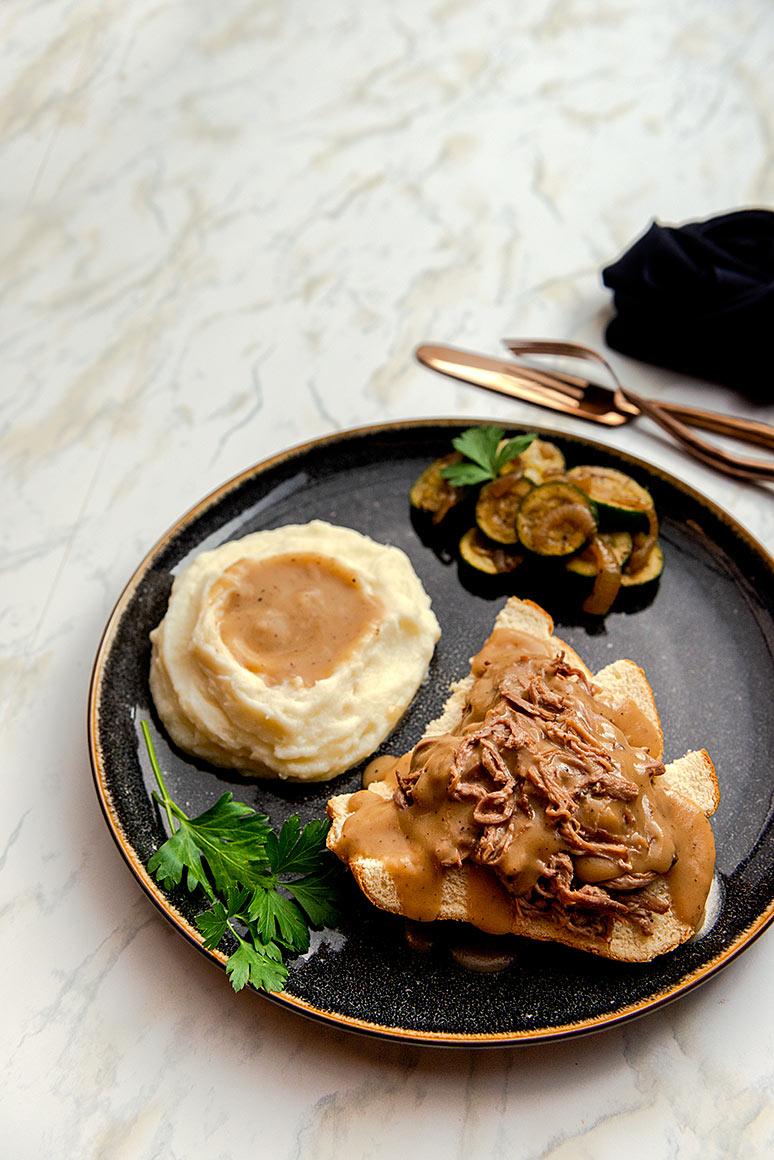 flat lay photo of beef sandwich, gravy, mashed potatoes and zucchini