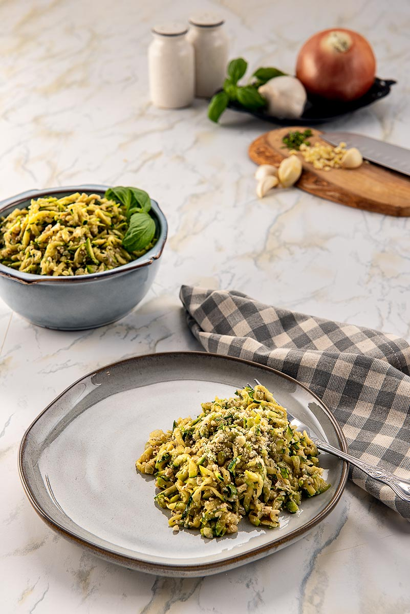 Two bowls of shredded zucchini and some ingredients.