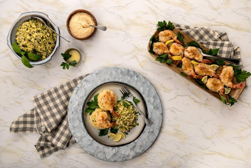 serving bowl of shredded zucchini, tray of parmesan shrimp, and dinner plate with shrimp, pasta and zucchini