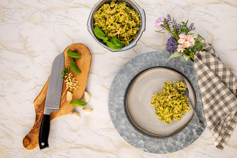 A serving bowl, charger, plate and serving of shredded zucchini and some ingredients.