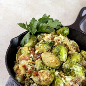 Prepared brussel sprouts in a cast iron skillet with parsley garnish.