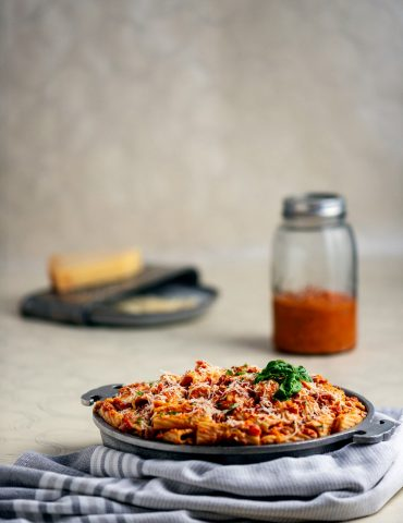 Serving bowl with pasta and vodka sauce. In the background is cheese and grater, small mason jar of pasta sauce.